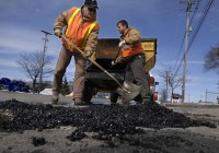 Crew Leader Denny Pitchellis and Equipment Operator Jeremy Turner fill giant potholes on Clyde Park in Wyoming, where there are now signs warning drivers of the hazardous road conditions. Press Photo/Katy Batdorff